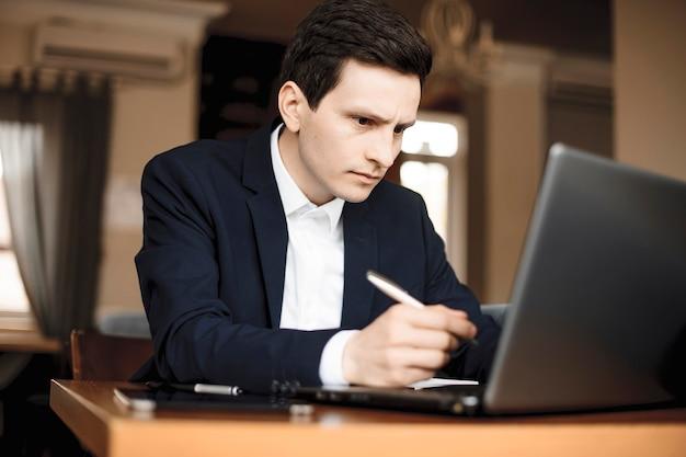 Close-up van een jonge blanke zakenman die in zijn kantoor werkt terwijl hij serieus naar zijn laptop kijkt.