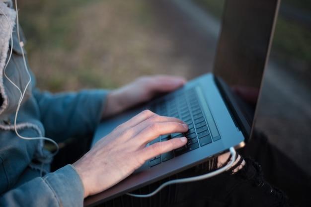 Close up van een jonge kerel zittend met laptop op benen