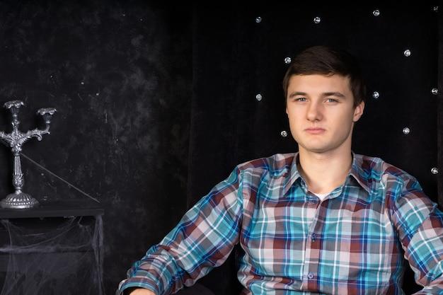 Close-up van een jonge man die in een pluche zwarte stoel met hoge rugleuning zit in de omgeving van een spookhuis