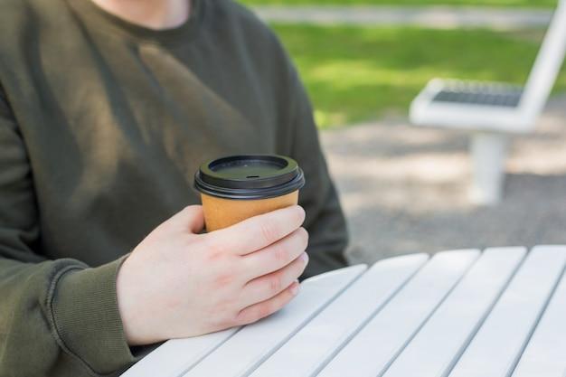 Close-up van een jonge man die koffie vasthoudt om mee te nemen in het zonnige park, zonlicht, onscherpe achtergrond. ruimte kopiëren.