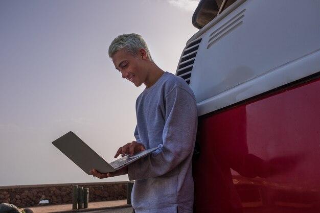 Close-up van een jonge man die 's avonds alleen zijn laptop en computer gebruikt met op zijn rug een rode en witte minibus - nomadentechnologiemensen die plezier hebben en genieten