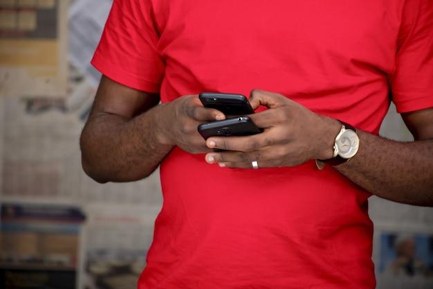 Close-up van een jonge man die twee telefoons in een kamer gebruikt