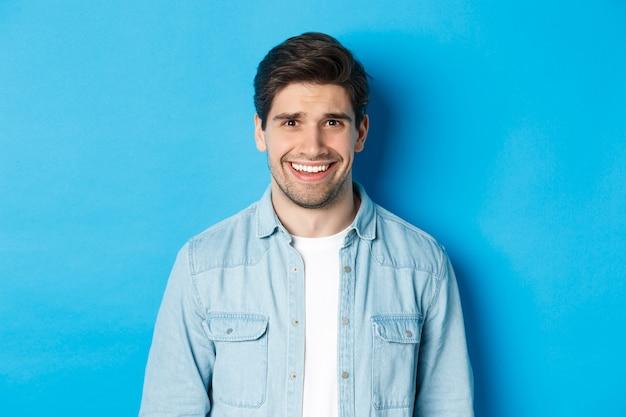 Close-up van een jonge man die zich ongemakkelijk voelt, glimlacht en ineenkrimpt van een ongemakkelijke situatie, staande over de blauwe muur