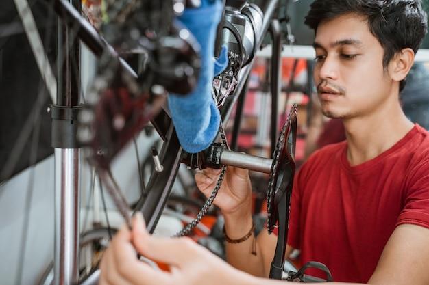 Close up van een jonge man in het rood die zorgvuldig fietsketting installeert