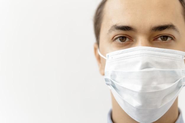 Close-up van een jonge man met een chirurgisch masker op zijn gezicht
