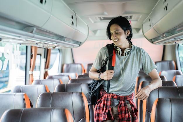 Close up van een jonge man met een rugzak en koptelefoon staan kijken naar zijn stoel terwijl hij in de bus