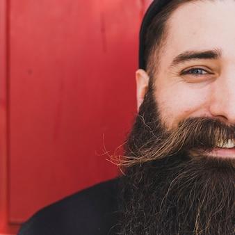 Close-up van een jonge man met snor en baard tegen rode achtergrond