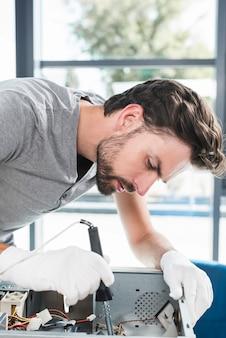 Close-up van een jonge mannelijke technicus die computer cpu herstelt