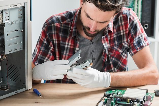 Close-up van een jonge mannelijke technicus die computergedeelte onderzoekt