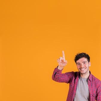 Close-up van een jonge mens die zijn vinger omhoog tegen oranje achtergrond richt