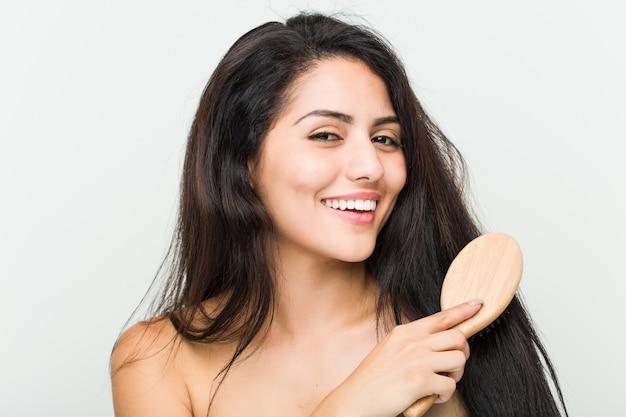 Close up van een jonge mooie en natuurlijke spaanse vrouw haar haren borstelen
