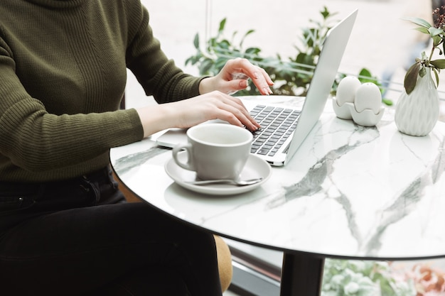Close-up van een jonge roodharige vrouw die binnen aan de cafétafel ontspant, koffie drinkt, op een laptop werkt