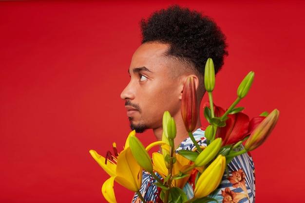 Close-up van een jonge rustige afro-amerikaanse man in hawaiiaans overhemd, houdt gele en rode bloemen boeket, staat op rode achtergrond.