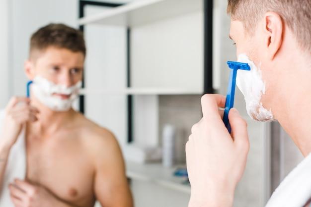 Close-up van een jonge shirtless man scheren met blauw scheerapparaat voor spiegel
