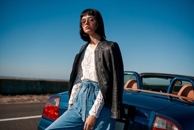 Close-up van een jonge stijlvolle vrouw met een kapsel die in de buurt van een auto zonder dak staat