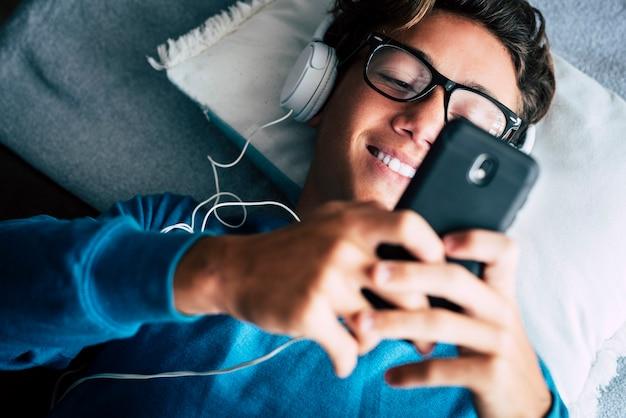 Close-up van een jonge telefoonverslaafde tiener die mobiel mobiel gebruikt, ligt thuis op de bank