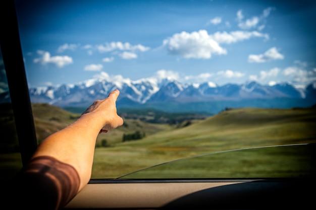 Close-up van een jonge toerist die zijn vinger de richting van het verkeer laat zien voor een verder avontuur