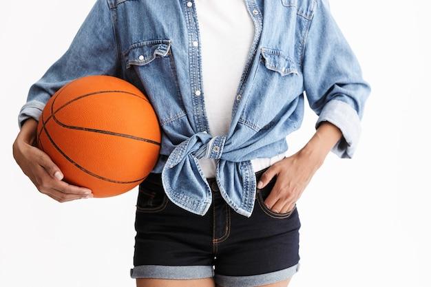Close-up van een jonge vrouw die casual denimkleding draagt, geïsoleerd over een witte muur, basketbal vasthoudt