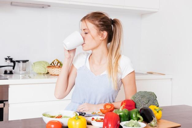 Close-up van een jonge vrouw die de koffie met verse kleurrijke groenten op houten lijst drinkt