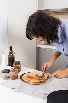 Close-up van een jonge vrouw die de pindakaas op pannekoek met mes en lepel uitspreidt