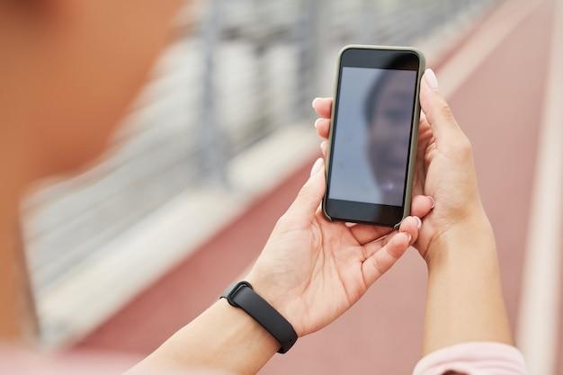 Close-up van een jonge vrouw die een mobiele telefoon voor haar houdt en buiten online praat