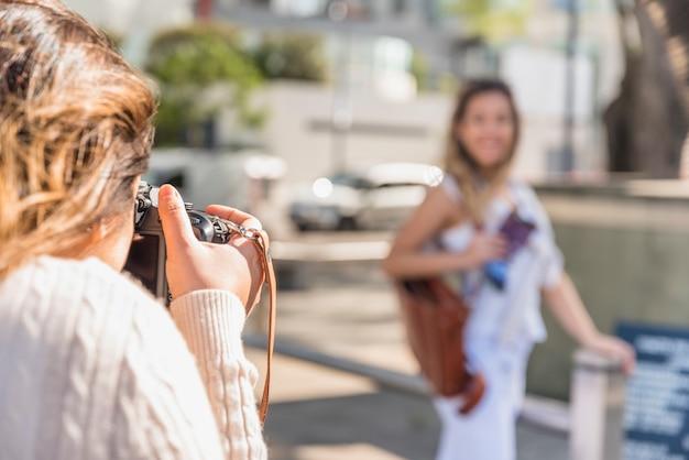 Close-up van een jonge vrouw die haar vrouwelijke vriend met camera fotografeert