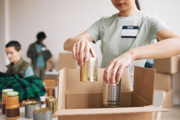 Close-up van een jonge vrouw die ingeblikt voedsel verpakt in dozen bij liefdadigheids- en donatiesevenementen, kopieer ruimte