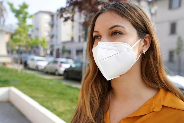 Close-up van een jonge vrouw die naar de zijkant kijkt terwijl ze buitenshuis een beschermend masker kn95 ffp2 draagt