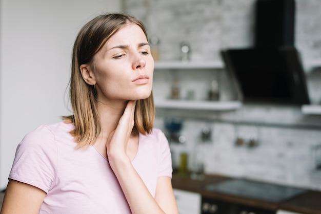 Close-up van een jonge vrouw die nekpijn heeft