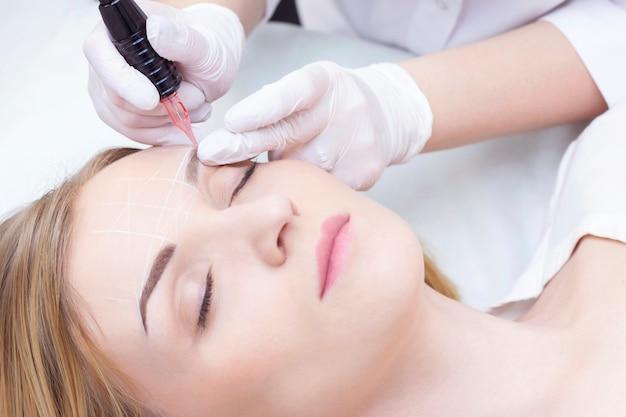 Close-up van een jonge vrouw die permanente wenkbrauwmake-up in een schoonheidssalon ondergaat