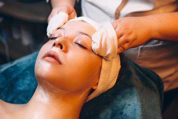 Close up van een jonge vrouw doet een gezichtstherapie in een wellness-spa door een schoonheidsspecialist.