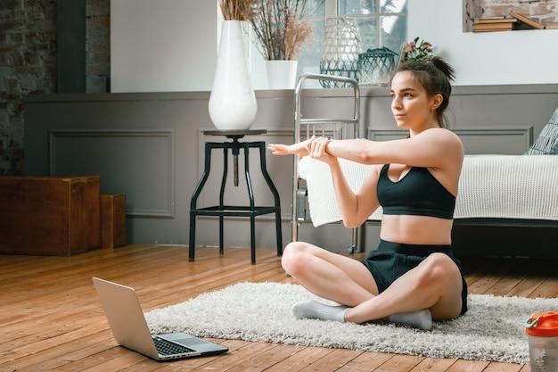 Close-up van een jonge vrouw in een sportuniform rust, strekt zich uit over de vloer thuis, kijkt naar een film en studeert vanaf een laptop, een sociaal netwerk