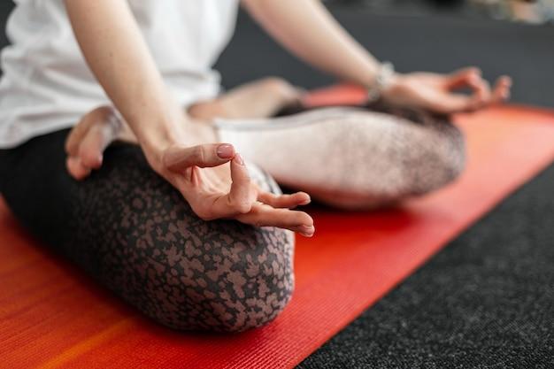 Close-up van een jonge vrouw in meditatie in de sportschool. yoga en gezonde levensstijl concept. vrije tijd.