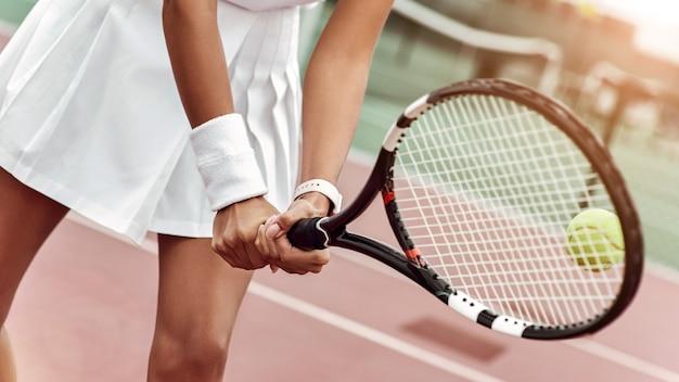 Close up van een jonge vrouw klaar om een tennisbal te slaan die een bal serveert