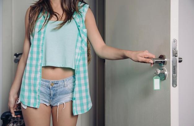 Close-up van een jonge vrouw met een geruit hemd en een korte spijkerbroek die een koffer vasthoudt en de deur van een hotelkamer opent. focus op hand en deurknop.
