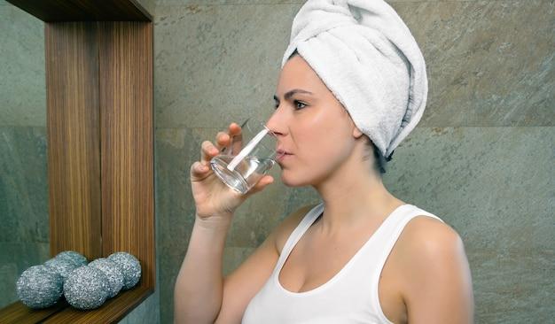 Close-up van een jonge vrouw met een handdoek over haar die een glas water drinkt in de badkamer. gezondheid en schoonheidsconcept.