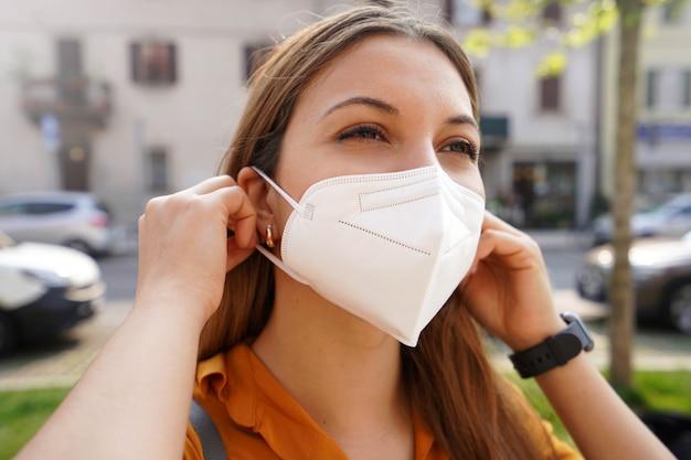 Close-up van een jonge vrouw met een medisch masker kn95 ffp2 in de straat van de stad. meisje zet buiten beschermend gezichtsmasker op.