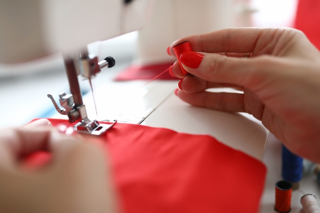 Close-up van een jonge vrouw met een spoel van rode draden professionele kleermaker die in de werkplaats werkt