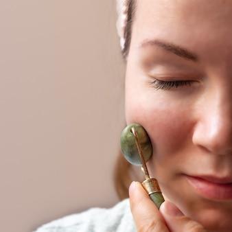 Close-up van een jonge vrouw met gesloten ogen die een stenen jade roller op haar gezicht houdt