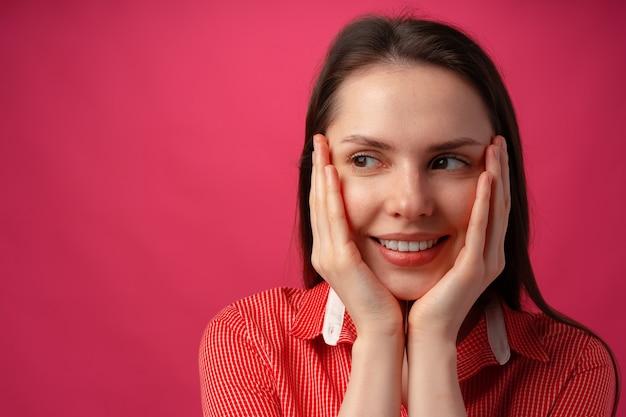 Close up van een jonge vrouw met gezicht in handen tegen roze achtergrond