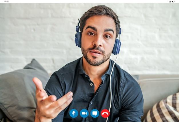 Close-up van een jonge zakenman die een werkvideogesprek voert terwijl hij thuis blijft. nieuwe normale levensstijl. bedrijfsconcept.
