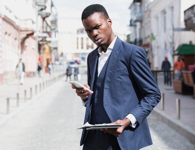 Close-up van een jonge zakenman klembord in de hand houden met behulp van de mobiele telefoon