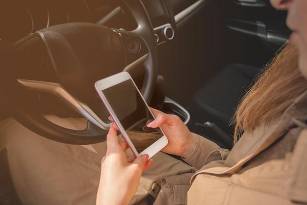 Close-up van een jonge zakenvrouw die haar smartphone bekijkt terwijl ze in de bestuurdersstoel van haar auto zit