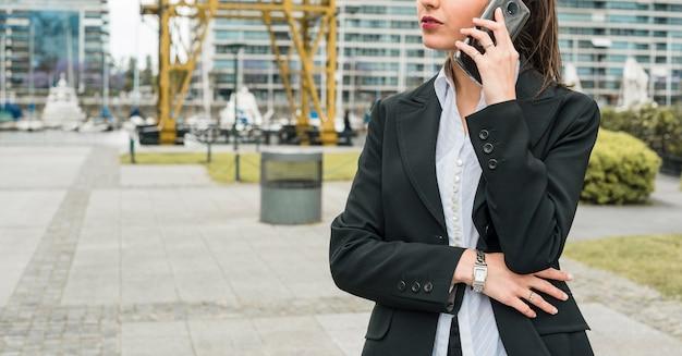 Close-up van een jonge zakenvrouw praten op mobiele telefoon in de open lucht
