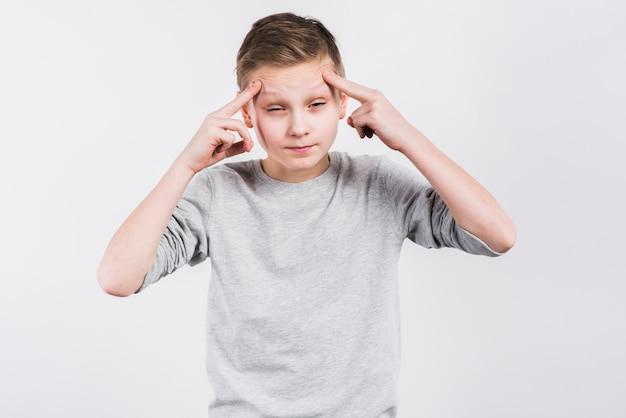 Close-up van een jongen die aan hoofdpijn tegen grijze achtergrond lijdt