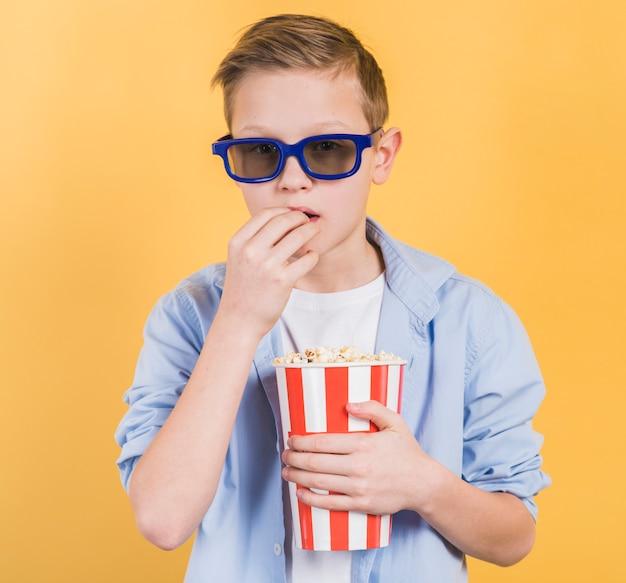 Close-up van een jongen die blauwe 3d glazen draagt die popcorns eten tegen gele achtergrond