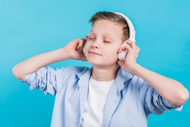 Close-up van een jongen die geniet van het luisteren muziek op witte hoofdtelefoon tegen blauwe achtergrond