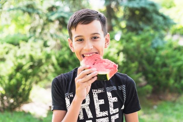 Close-up van een jongen die watermeloenplak in het park eet