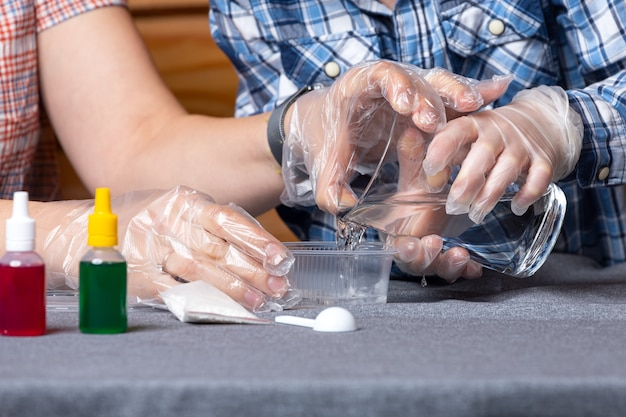 Close-up van een jongen en zijn moeder, wetenschappers gieten water in een bak met chemische elementen