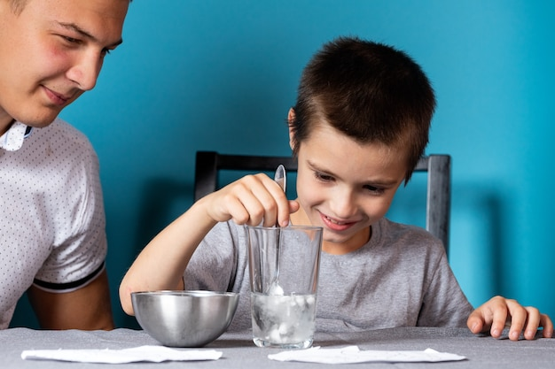 Close-up van een jongen in een grijs t-shirt wast een penseel van aquarelverf op een blauwe achtergrond